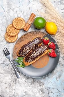 ライトテーブルのデザートケーキクッキーにクッキーを添えたトップビューのおいしいチョコエクレア