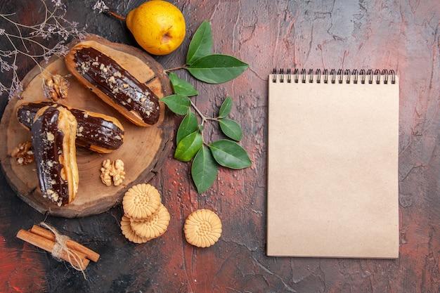 ダークテーブルのデザートケーキの甘いクッキーとトップビューのおいしいチョコエクレア