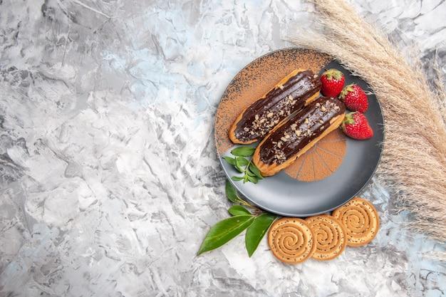 Вид сверху вкусные шоколадные эклеры с печеньем на белом столе, торт, печенье, десерт
