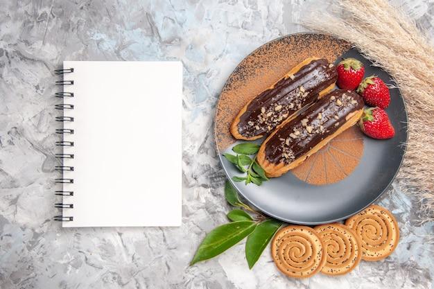 Vista dall'alto deliziosi bignè al cioccolato con biscotti su un dessert di biscotti con torta da tavola bianca