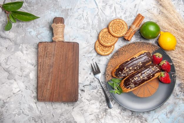 Vista dall'alto deliziosi bignè al cioccolato con biscotti su un biscotto da dessert con torta da tavola bianca