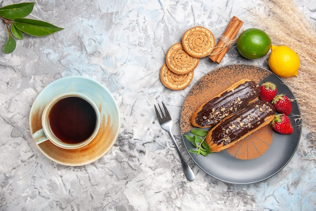 Top view delicious choco eclairs with cookies on the white table cake dessert cookie