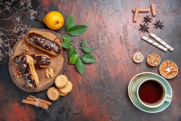 Top view delicious choco eclairs with cup of tea on a dark table dessert sweet cake