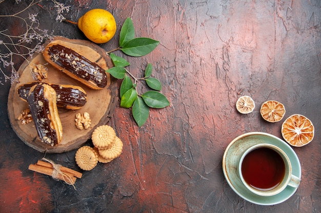 Top view delicious choco eclairs with cup of tea on dark table dessert sweet cake