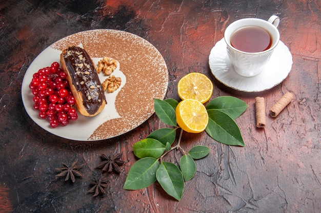 Top view delicious choco eclairs with cup of tea on a dark table pie dessert cake sweet