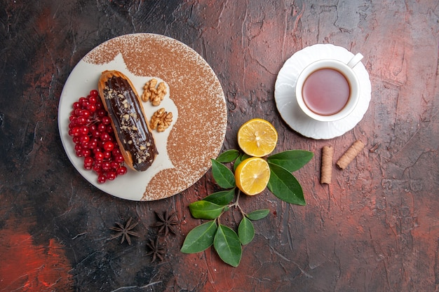 Top view delicious choco eclairs with cup of tea on dark table pie dessert cake sweet