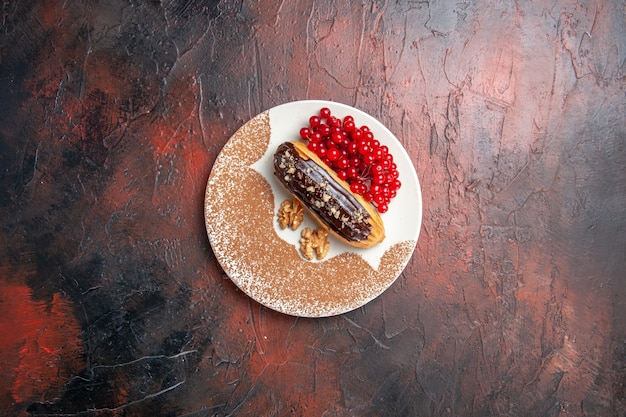 Top view delicious choco eclairs with red berries on a dark table pie dessert cake sweet