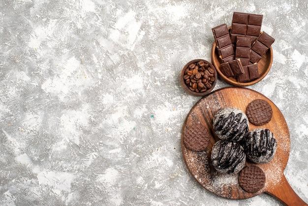 Vista dall'alto di deliziose torte di palline di cioccolato con biscotti sulla superficie bianca chiara