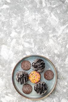 Vista dall'alto di deliziose torte di palline di cioccolato con i biscotti sulla superficie bianca
