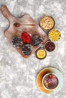 Vista dall'alto di deliziose torte di palline di cioccolato con una tazza di tè sulla superficie bianca