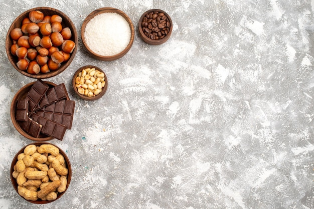 Top view of delicious chocolate bars with hazelnuts and peanuts on a white surface