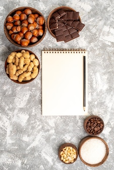 Vista dall'alto di deliziose barrette di cioccolato con nocciole e arachidi sulla superficie bianca