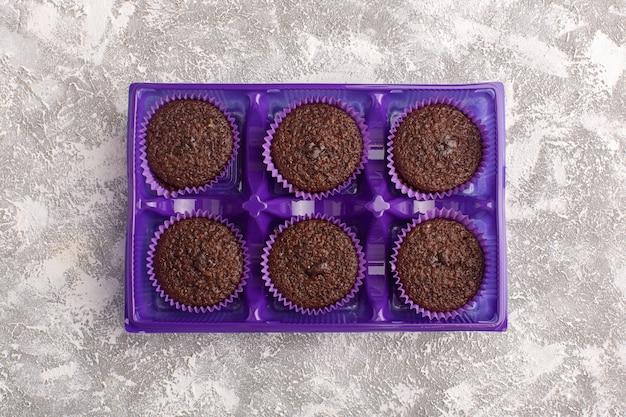 Вид сверху вкусные шоколадные пирожные внутри фиолетовой упаковки на светлом фоне сладкое тесто для выпечки шоколадное