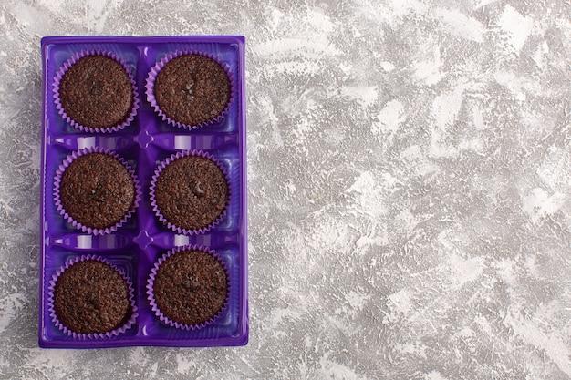 Вид сверху вкусных шоколадных пирожных внутри фиолетовой упаковки на светлом столе, торт, шоколадный чай, выпечка, тесто
