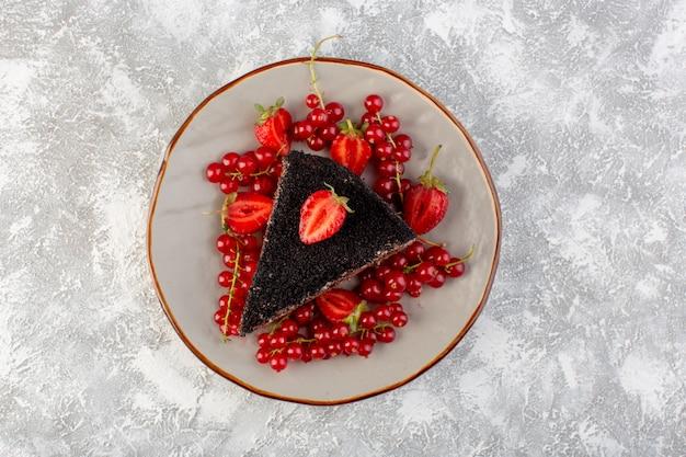 明るい背景のケーキビスケット生地を焼く上にチョコクリームと新鮮な赤いクランベリーでスライスしたおいしいチョコレートケーキのトップビュー
