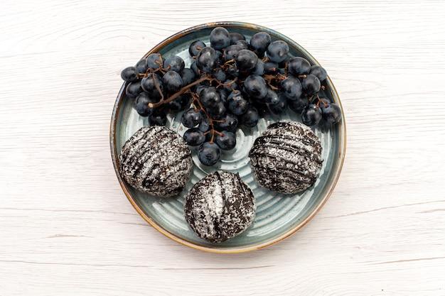 上面図白い背景の上の黒ブドウとおいしいチョコレートケーキケーキビスケット甘い砂糖パイフルーツ