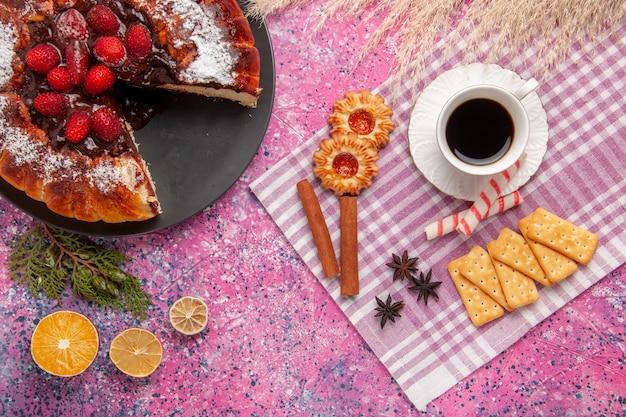 Вид сверху вкусный шоколадный торт с печеньем, крекерами и чашкой чая на розовом столе, сахарный сладкий бисквитный торт