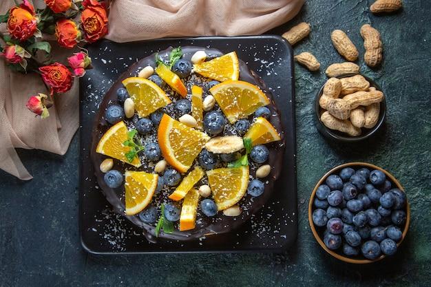 Vista dall'alto deliziosa torta al cioccolato con frutta fresca su fondo scuro