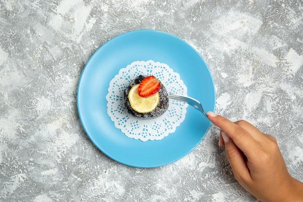 上面図白い表面にアイシングが付いたおいしいチョコレートケーキチョコレートシュガービスケット甘いケーキクッキー