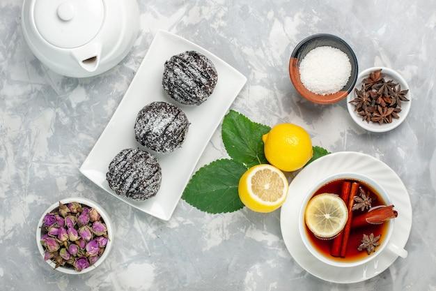 Вид сверху вкусные шоколадные пирожные, маленькие круглые, с лимоном и чашкой чая на белой поверхности, фруктовый торт, печенье, сладкое сахарное печенье