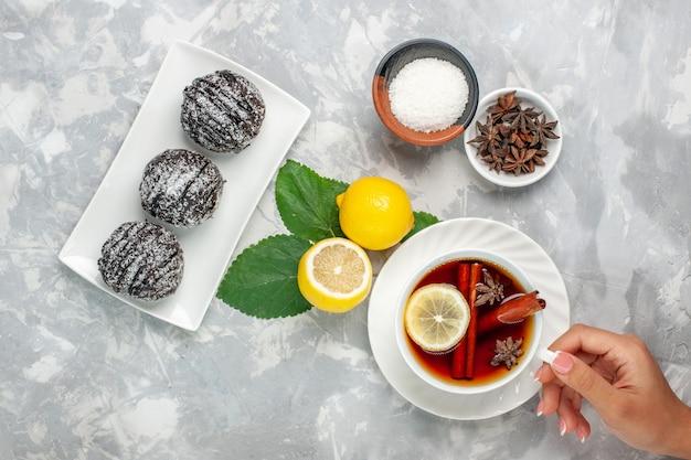 Vista dall'alto deliziose torte al cioccolato piccolo tondo formato con limone e tazza di tè sulla superficie bianca frutta torta biscotto zucchero dolce cuocere biscotto
