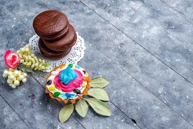Vista dall'alto di deliziose torte al cioccolato rotonde formate con torta alla crema isolato su grigio, cuocere al forno torta al cacao zucchero dolce biscotto