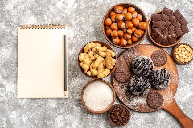 Vista dall'alto di deliziose torte al cioccolato con biscotti noci e arachidi sulla superficie bianca