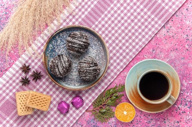 Vista dall'alto deliziose torte al cioccolato con una tazza di tè e cialde sul rosa