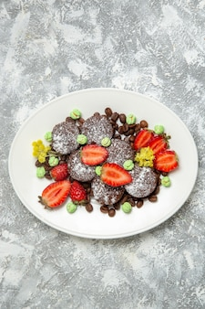上面図白い表面に新鮮なイチゴのおいしいチョコレートケーキビスケットシュガーケーキスウィートティークッキー