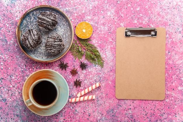 Vista dall'alto deliziose torte al cioccolato con glassa e tazza di tè sul rosa
