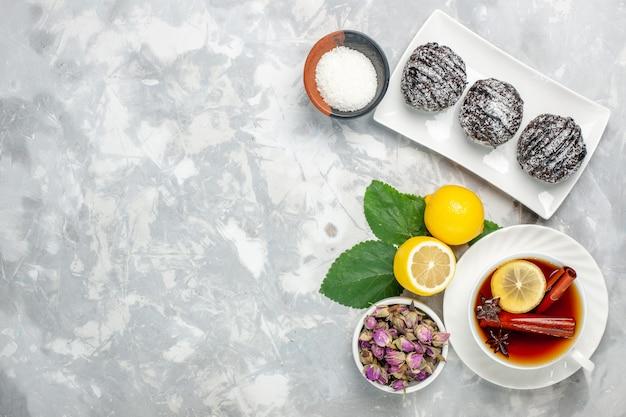 Vista dall'alto deliziose torte al cioccolato con limone e tazza di tè sulla superficie bianca frutta torta biscotto zucchero dolce cuocere biscotto