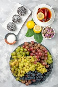 上面図白い表面にレモンティーとブドウのおいしいチョコレートケーキフルーツケーキビスケット甘い砂糖焼きクッキー