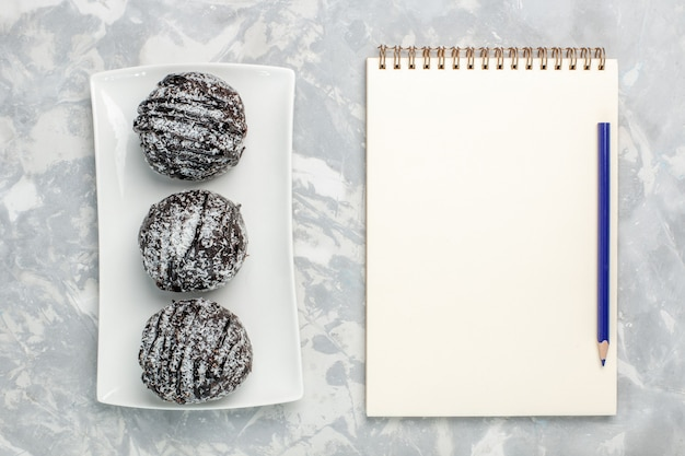 Vista dall'alto deliziose torte al cioccolato con glassa bianca sulla superficie bianca chiara torta biscotto cuocere al cioccolato dolce zucchero tè