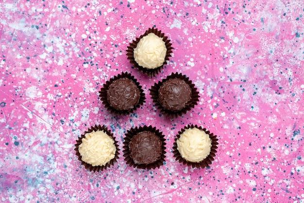 Вид сверху вкусные шоколадные конфеты из белого и темного шоколада на розовом фоне.