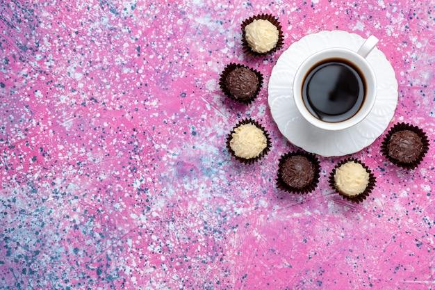 Vista dall'alto deliziose caramelle al cioccolato bianco e cioccolato fondente con una tazza di tè sullo sfondo rosa.