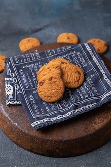 Вид сверху вкусное шоколадное печенье запеченное и вкусное на темно-сером фоне печенье бисквит сладкий чай