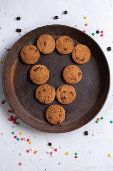 Вид сверху вкусного шоколадного печенья внутри коричневой круглой тарелки и выложенного на белом фоне печенья, сахара, сладкого чая