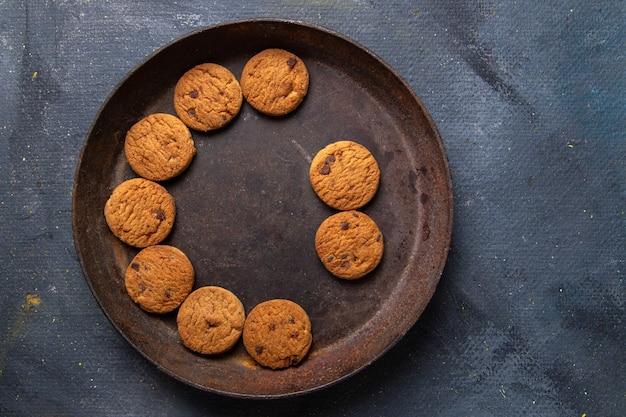 Вид сверху вкусного шоколадного печенья внутри коричневой круглой тарелки на темно-сером фоне печенье печенье сладкий сахарный чай