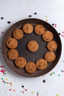 Вид сверху вкусного шоколадного печенья внутри коричневой круглой тарелки на белом фоне печенье печенье сахар сладкий чай