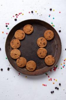 Вид сверху вкусного шоколадного печенья внутри коричневой круглой тарелки на белом фоне печенье, бисквит, сладкий чай