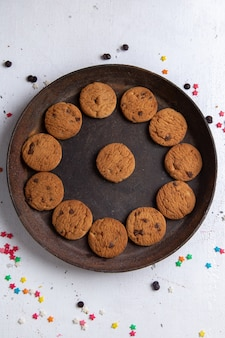 Top view delicious chocolate cookies inside brown round plate on the white background cookie biscuit sugar sweet tea