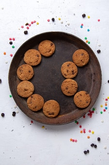 Top view delicious chocolate cookies inside brown round plate on the white background cookie biscuit sweet tea