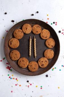 Vista dall'alto deliziosi biscotti al cioccolato all'interno del piatto rotondo marrone con candele sullo sfondo bianco biscotto biscotto zucchero tè dolce