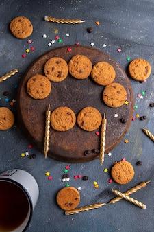 Вид сверху вкусное шоколадное печенье со свечами и чаем на темно-сером фоне печенье бисквит чай сладкий
