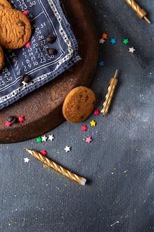 Vista dall'alto deliziosi biscotti al cioccolato con candele sul tè dolce biscotto sfondo grigio scuro