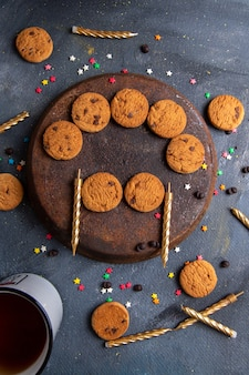 Vista dall'alto deliziosi biscotti al cioccolato con candele e tè sullo sfondo grigio scuro biscotto biscotto tè dolce