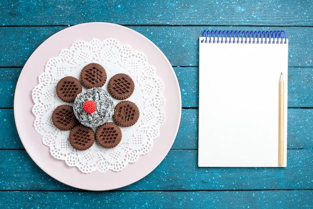 上面図青い素朴な机の上のチョコレートケーキとおいしいチョコレートクッキービスケットティークッキー甘いケーキ砂糖