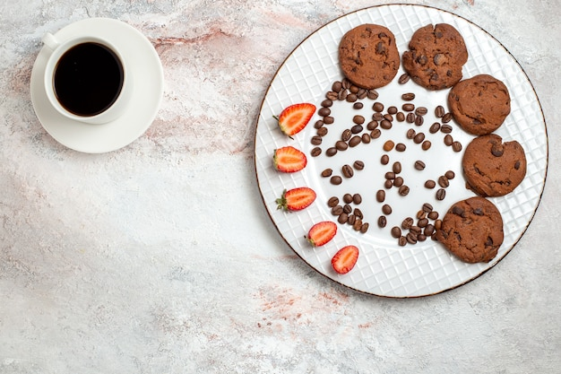 Вид сверху вкусное шоколадное печенье с шоколадной крошкой, кофе и клубникой на белом фоне, печенье, сахар, сладкий торт, печенье