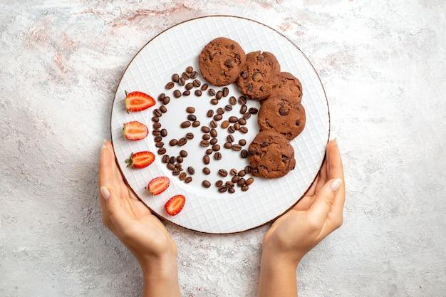 Vista dall'alto deliziosi biscotti al cioccolato con scaglie di cioccolato e fragole sulla superficie bianca biscotto zucchero dolce cuocere i biscotti della torta