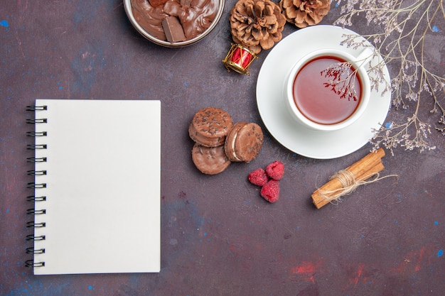 暗い背景の上のお茶とおいしいチョコレートクッキーの上面図パイビスケット甘いケーキクッキーティー